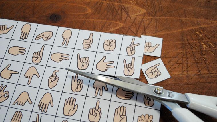 指文字表をハサミで切っている
